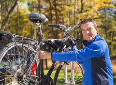 Man putting bicycle onto bike rack - stock photo