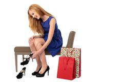Smiling woman deciding on a new pair of shoes Stock Photos