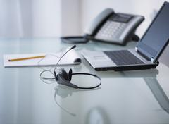 View of headset, telephone, laptop and paper material on desk - stock photo