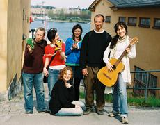 Laleh Pourkarim poses with acoustic guitar and others in theater project. Stock Photos