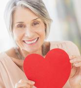 Stock Photo of Portrait of woman holding paper heart