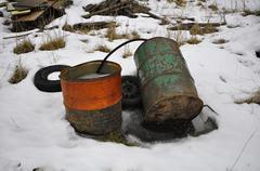 Barrels in Swedish winter junk yard - stock photo