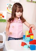 child playing with wood  block  in  room. - stock photo