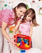 child with wood block and construction set in play room. - stock photo