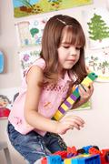 Stock Photo of child with  block and construction set in play room.