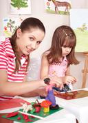 mother and  daughter playing plasticine. - stock photo