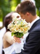bride and groom giving flower outdoor. - stock photo