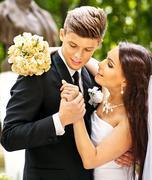 Stock Photo of groom embrace bride .
