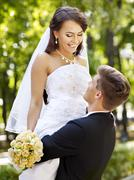 bride and groom with flower outdoor. - stock photo