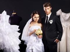 Couple try wedding dress in shop. Stock Photos