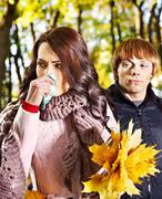 couple sneezing  autumn outdoor. - stock photo
