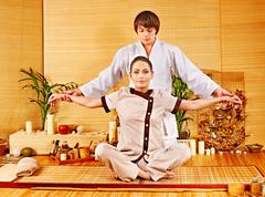 Male masseur doing massage woman in bamboo spa. Stock Photos