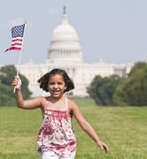 Stock Photo of USA, Washington DC, girl (10-11) with US flag running in front of Capitol