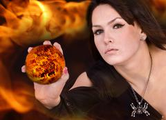 witch in black dress with fire ball on flame. - stock photo