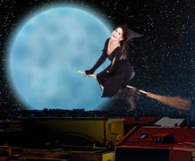 Girl witch fly over  city against moon and star sky. Stock Photos