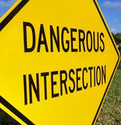 Close up of Dangerous Intersection sign - stock photo