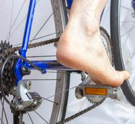 riding a bike with bare foot. - stock photo