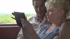 Happy romantic young couple play digital tablet computer train entertainment fun Stock Footage