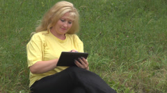 Young happy businesswoman working on computer tablet garden, meadow holiday girl Stock Footage