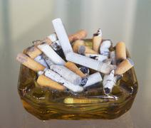 Ashtray filled with many cigarette butts Stock Photos