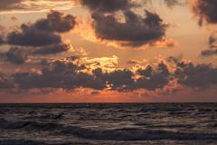 Orange sun behind clouds over the sea. - stock photo