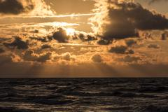 Sun behind clouds over the sea. - stock photo