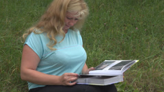 Beautiful woman looking at her photo on album lady garden summer attractive  Stock Footage