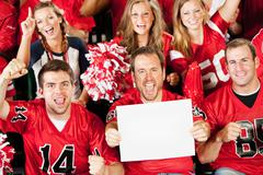 Fans: man holds small blank sign as group cheers to camera Stock Photos