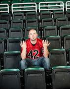 Stock Photo of fans: lonely fan unsure of why team lost