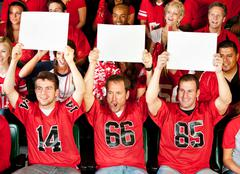 fans: guys holding up small blank signs - stock photo
