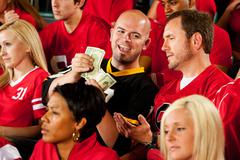 fans: visiting team fan counts money from bet - stock photo