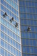 Window washers cleaning windows on skyscraper Stock Photos