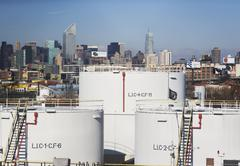 USA, New York City, Oil storage tanks in refinery with Manhattan skyline in - stock photo