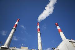 USA, New York City, Factory chimneys against blue sky - stock photo