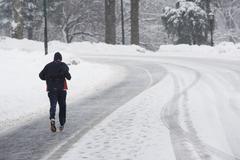USA, New York City, man jogging up snowy road Stock Photos