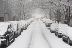 Stock Photo of USA, New York City, snowy street with rows of parked cars