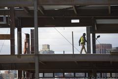 USA, New York City, Construction worker walking inside of unfinished structure Stock Photos