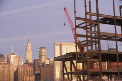 USA, New York City, Crane with unfinished structure and Manhattan skyline in Stock Photos