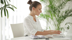 Attractive woman sitting at table using laptop and writing in notebook Stock Footage