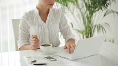 Businesswoman sitting at table with cup of cofee and using laptop with smile. Stock Footage