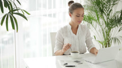 Businesswoman sitting at table with cup of cofee and using laptop Stock Footage