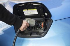 Close-up of man charging electric car - stock photo
