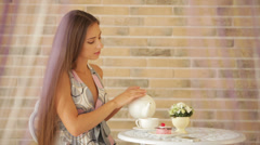 Beautiful young girl sitting at cafe and pouring tea into cup Stock Footage