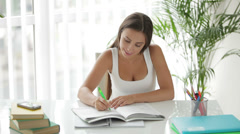 Charming girl sitting at table and writing in notebook Stock Footage