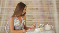 Charming young girl sitting at cafe and using cellphone and eating cake Stock Footage