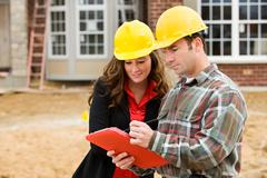 construction: contractor points out things on checklist - stock photo