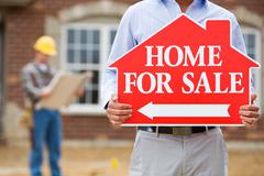 Stock Photo of construction: agent at open house holds sign