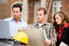 construction: group studies blueprints and computer plans - stock photo