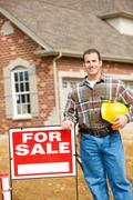 construction: builder stands by sale sign - stock photo