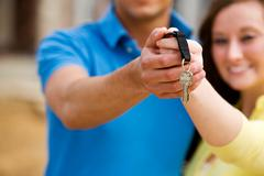 Construction: couple holds out house keys Stock Photos